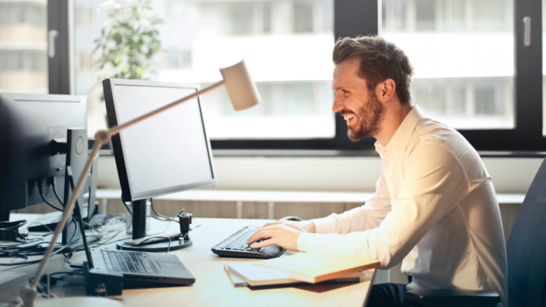 Man smiling while on computer