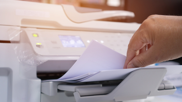 Business Documents concept : Businesswoman hands working in process press of paper in laser printer on busy work desk office. Soft focus