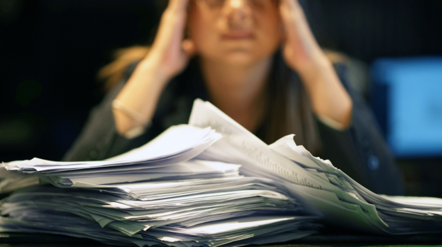 Close-up of office worker is distressed with a lot of paperwork in front of her. A lot of paper work in office. Yelling and screaming for bad results. Businesswoman in problems.