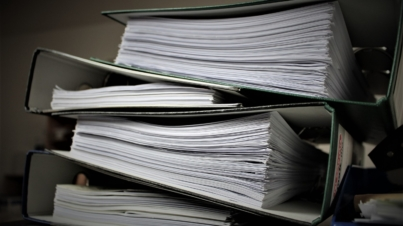 Stack of business documents in binders waiting to be shredded.